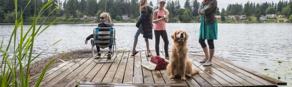 Group of girls and a dog fishing on a lake